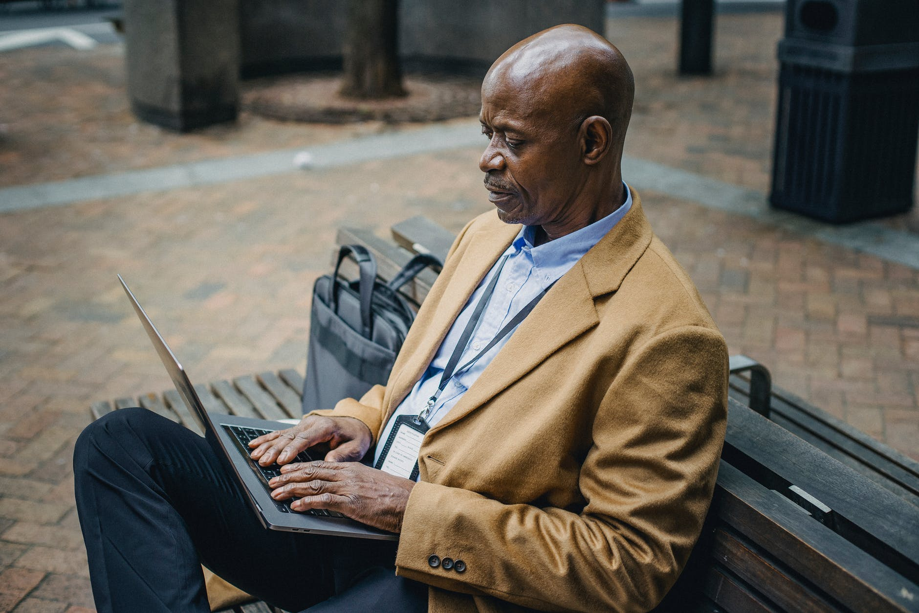 focused black businessman typing on laptop in town